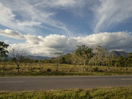 Blue sky and dramatic clouds over the landscape of Cuba, by the side of a highway