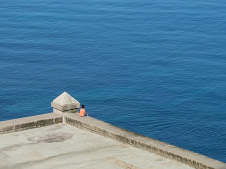 One woman sat alone on the sea wall, Malecon, Havana, Cuba, looking at a perfectly calm blue Atlantic Ocean