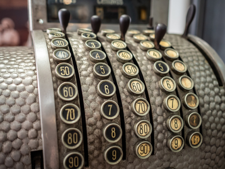 Antique cash register with numbered buttons and lever, with textured metal body