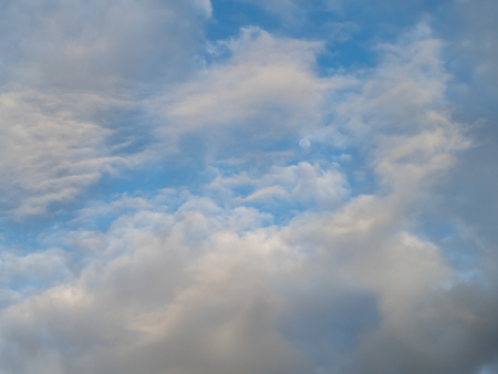 Afternoon cloudscape against blue sky with a glimpse of the moon