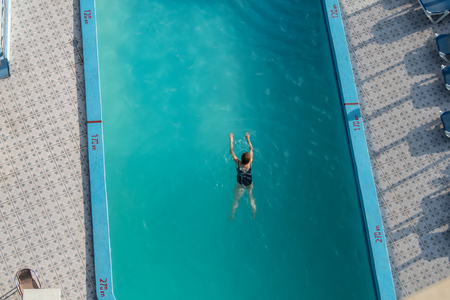 Aerial view of an older caucasian woman swimming in a blue hotel pool Stock Photo