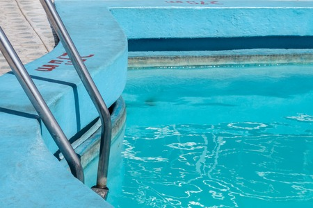 Poolside in Havana, blue pool with rippled water and ladder