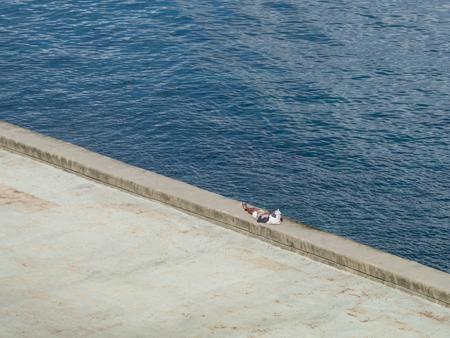Man alone taking a break on the sea wall of the Malecon in Havana, Cuba
