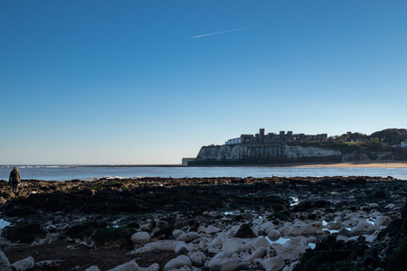 People walking on the beach and rocks at evening in Kingsgate Bay, Broadstairs, Kent, with Kingsgate Castle in the distance