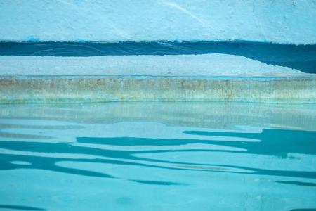 Detail of water rippling in blue swimming pool and reflections on the side