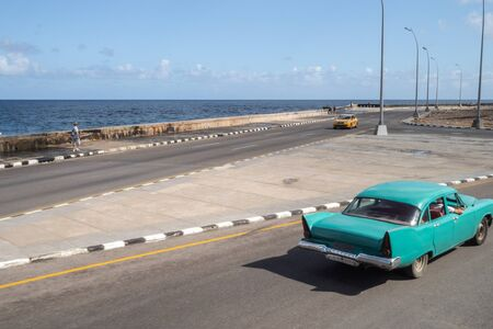 Turquoise vintage car driving down the Malecon, Havana, Cuba, with sea and horizon in the distance