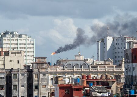 View over rooftops in Old Havana, with oil refinery flame, tower and smoke pollution