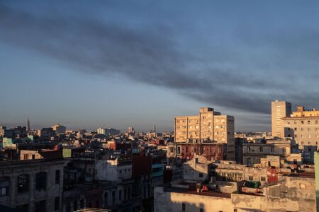 Golden light on the buildings of UNESCO site of Old Havana, with smoky clouds in the sky 免版税图像