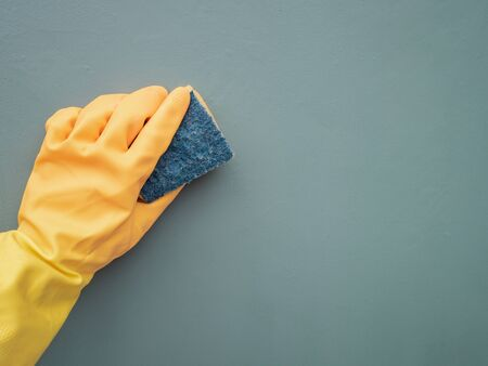Hands wearing yellow rubber gloves, cleaning a green wall with a scourer