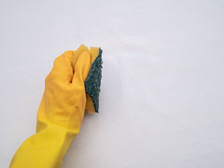 Hands wearing bright yellow rubber gloves on a white cloth background