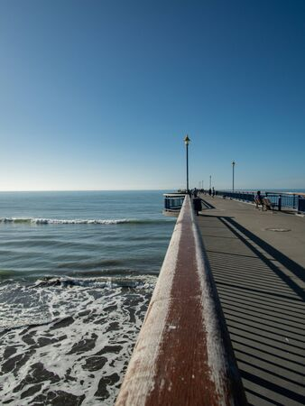Modern New Brighton pier, New Zealand South Island, with horizon behind and incidental people
