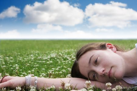 young girl laying in field photo