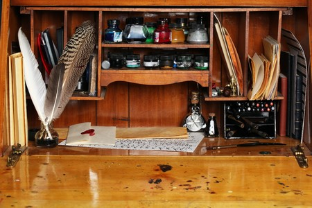 Old writing desk full of quills & inks for calligraphy photo