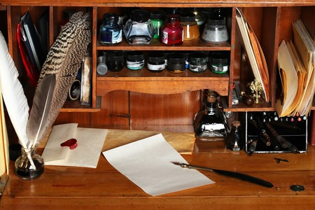 antique paper: Old writing desk full of quills & inks for calligraphy