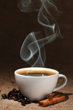 Coffee cup with coffee beans and cinnamon Imagens