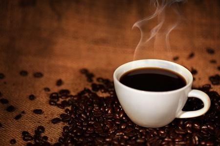 Kopje koffie op gebrande koffiebonen