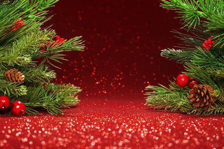 spruce: Christmas tree branches on glittering red background