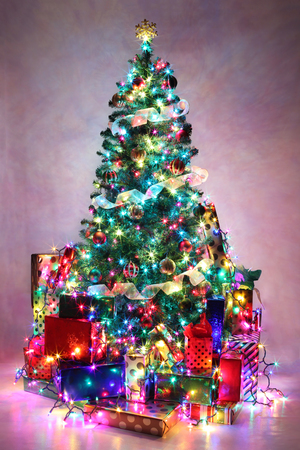 decorated: Decorated Christmas tree with colorful lights surrounded by presents.