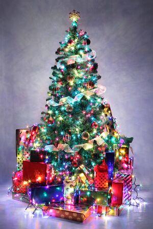 cajas navide�as: �rbol de Navidad decorado con luces de colores rodeado de regalos.