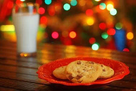 christmas cookies: Cookies and milk for Santa Claus in front of a Christmas tree
