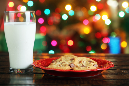 galletas de navidad: Cookies and milk for Santa Claus in front of a Christmas tree