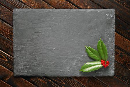 dark grey slate: Holly with berries on dark stone background