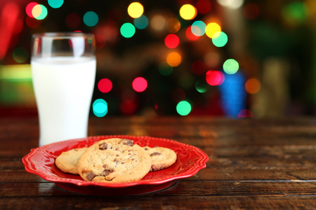 Cookies and milk for Santa Claus in front of a Christmas tree