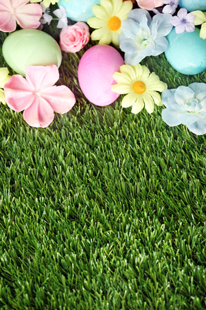 egg hunt: Colorful Easter eggs on grass with flowers background Stock Photo