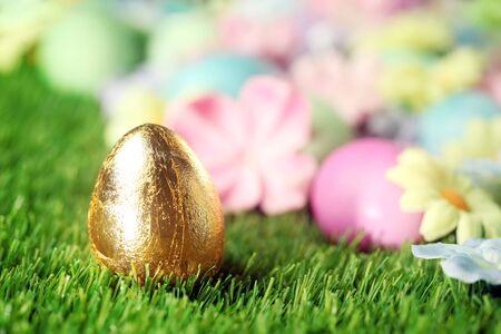 osterei: Bunte Ostereier auf Gras mit goldenen Ei