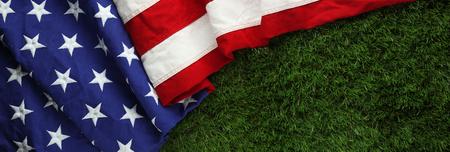 記念日や退役軍人の日のバック グラウンドの芝生の上の赤、白、および青のアメリカ国旗