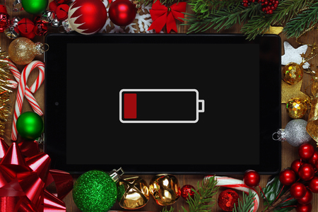 Tablet with low battery surrounded with Christmas decorations