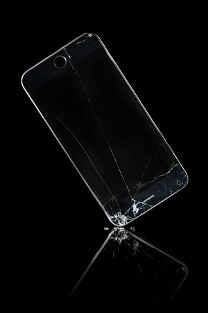 Broken phone with a shattered screen background Stock Photo