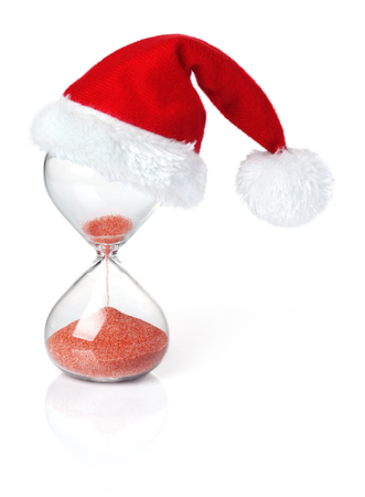 Hourglass with Christmas Santa hat showing the passage of time Stock Photo