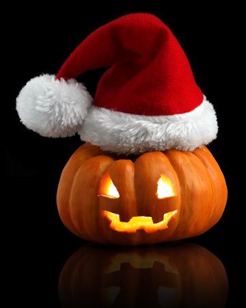 Single orange pumpkin Jack-o-lantern with Christmas Santa hat isolated on black