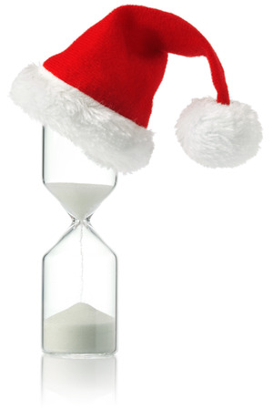 Hourglass with Christmas Santa hat showing the passage of time Stock Photo - 110697309