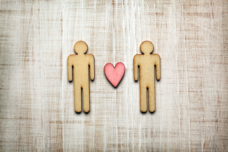 Two men with heart on wooden background