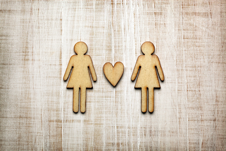 Two women with heart on wooden background