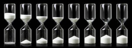 Collection of hourglasses with white sand showing the passage of time