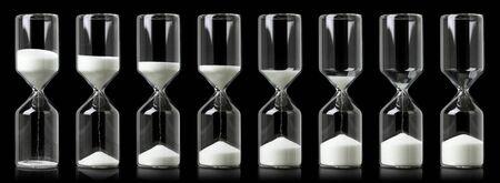Sammlung von Sanduhren mit weißem Sand, die den Lauf der Zeit zeigen