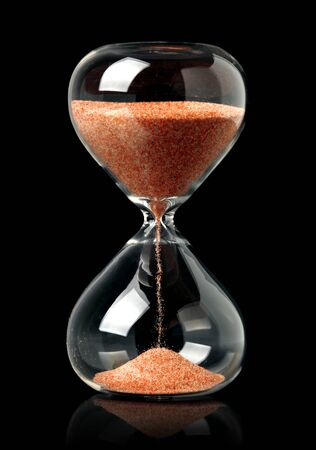 Hourglass with red sand showing the passage of time Stock Photo