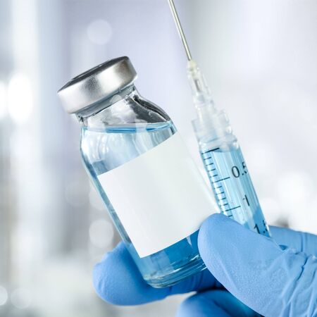 Healthcare concept with a hand in blue medical gloves holding a vaccine vial with blue liquid and black white label Stock Photo