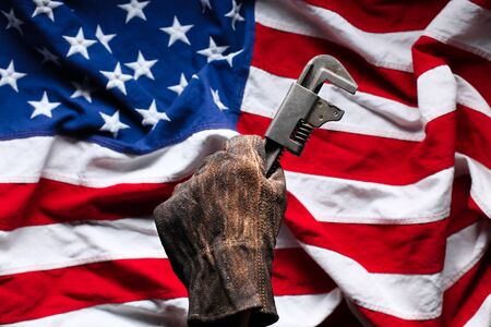 Hand in worn and dirty golve holding pipe wrench over American Flag