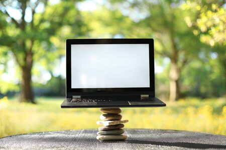 Laptop with blank screen outdoors balancing on stones surrounded by trees. Nature vs work life balance concept.