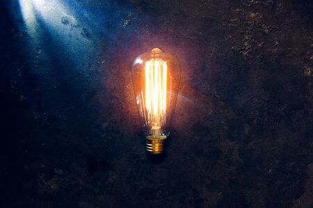 Vintage old light bulb glowing yellow on rough dark background. Idea, creativity concept. 스톡 콘텐츠