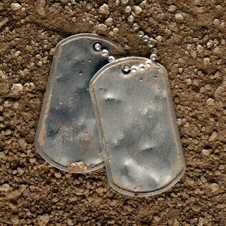 Dented and worn blank military dog tags fallen in dirt