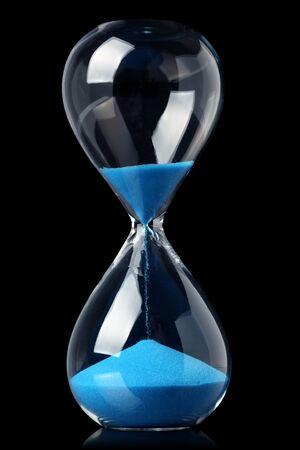 Sablier avec du sable bleu montrant le passage du temps