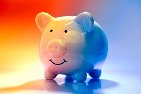 Smiling Piggybank on red and blue background. Saving vs spending money concept. Stock fotó
