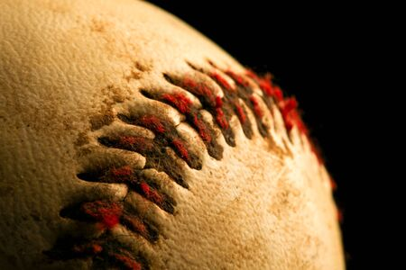 Close up of old worn baseball showing dirty red stitches.