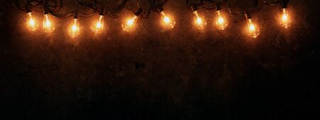 Row of lit string light bulbs glowing on dark grungy background.