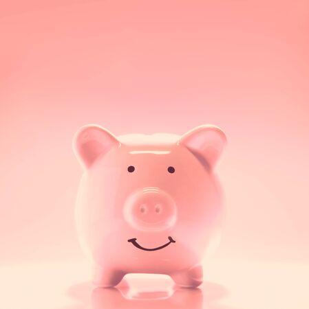 Smiling Piggybank on pink background. Saving money concept.